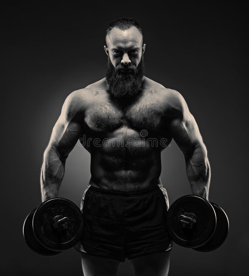 Alimenti l'uomo barbuto atletico nell'addestramento che pompa su muscles con immagini stock libere da diritti