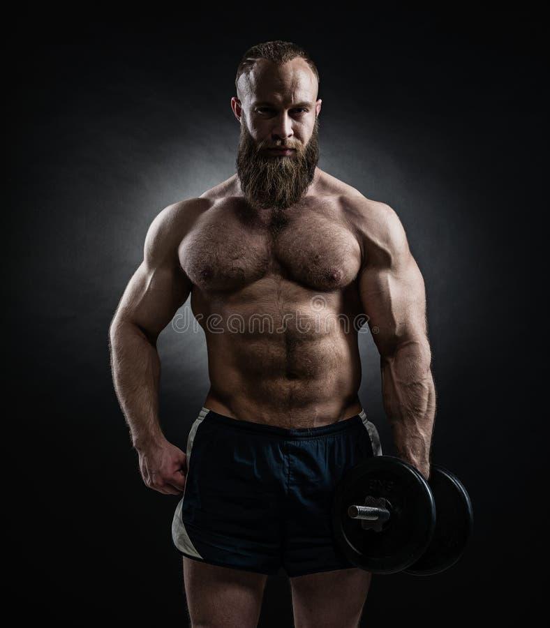 Alimenti l'uomo barbuto atletico nell'addestramento che pompa su muscles con la d fotografie stock