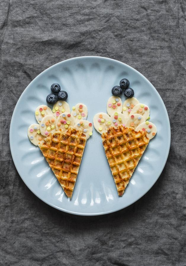 Alimenti per bambini creativi di divertimento Cialde con la banana ed i mirtilli su un fondo grigio, vista superiore L'alimento a immagine stock libera da diritti