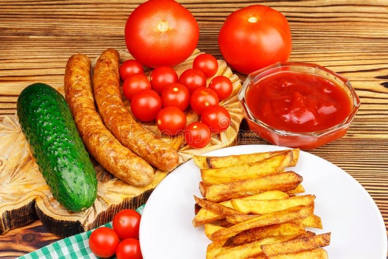 Alimenti a rapida preparazione casalinghi, porzione di patate fritte, ketchup, salsiccie arrostite e pomodoro ciliegia sul bordo  fotografie stock libere da diritti
