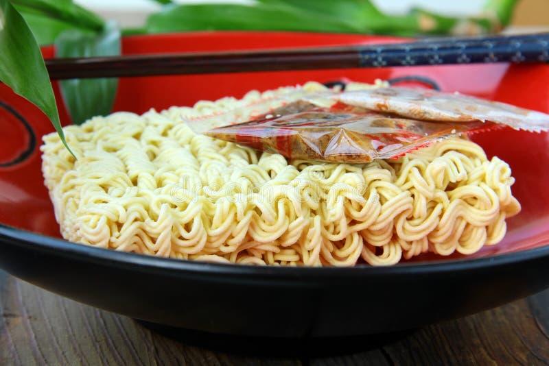 Alimenti a rapida preparazione della tagliatella asiatica istante con le bacchette fotografia stock