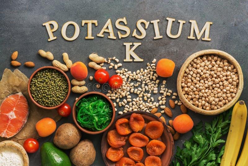 Alimenti ricchi in potassio, salmone, legumi, verdure, frutti su un fondo scuro Concetto sano dell'alimento, prevenzione dell'avi immagine stock libera da diritti