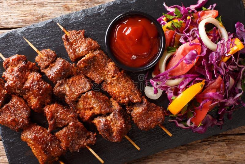 Alimento africano: no espeto picante do suya em espetos com legume fresco s fotos de stock
