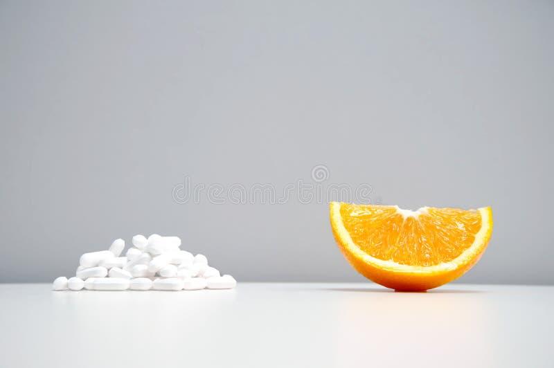 Alimento alaranjado cortado do fruto para a saúde com os comprimidos brancos da droga para imagens de stock royalty free