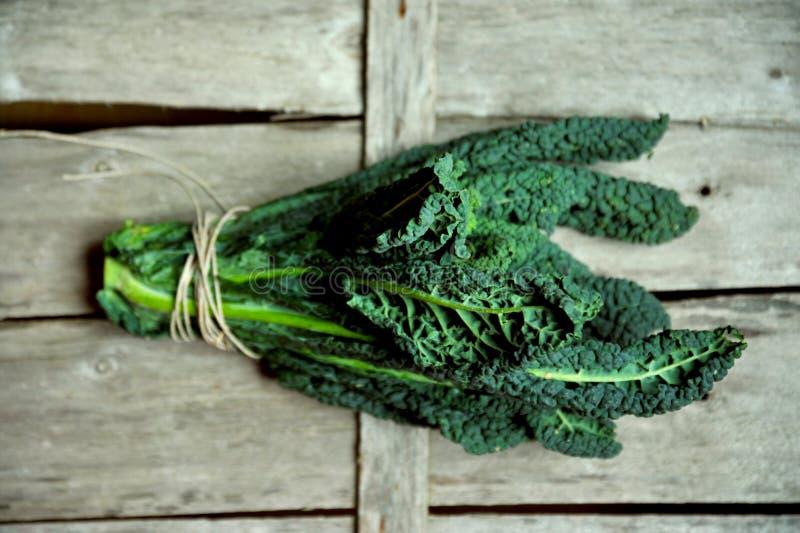 Alimento alcalino e sano: foglie del cavolo su un fondo d'annata immagine stock