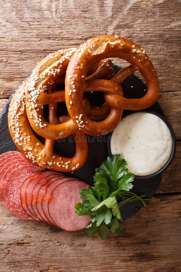 Alimento alemão: salsichas e pretzeis cortados com fim do molho de creme imagens de stock