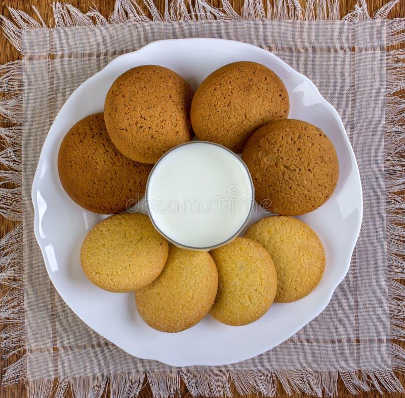 Alimento, alimentos sem valor nutritivo, culinário, cozimento e conceito comer - cookies de farinha de aveia e vidro de leite asc imagem de stock royalty free