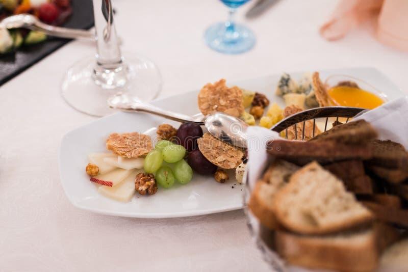 Alimento apetitoso em uma tabela de banquete: uva, queijo, porcas, petiscos foto de stock royalty free