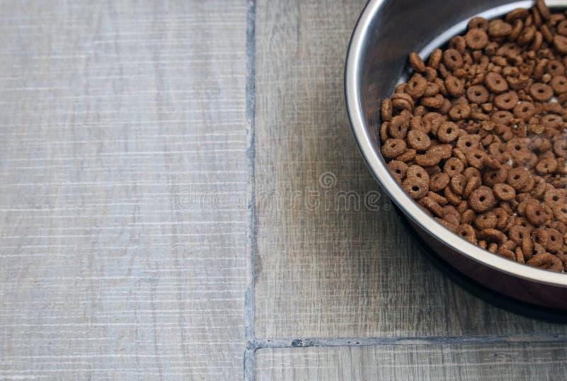 Alimento asciutto per i gatti ed i cani in piatto di alluminio sul fondo del pavimento fotografie stock