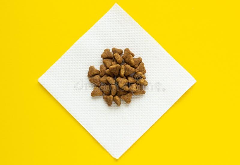 Alimento asciutto per i gatti, su un tovagliolo su un fondo giallo fotografia stock libera da diritti
