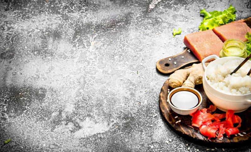 Alimento asiático Arroz con un pedazo de salsa de los salmones y de soja en un fondo rústico imagenes de archivo