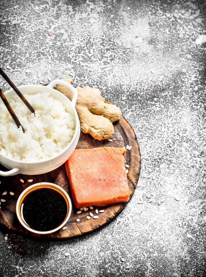 Alimento asiático Arroz hervido con un pedazo de salsa de los salmones y de soja En fondo rústico fotos de archivo libres de regalías