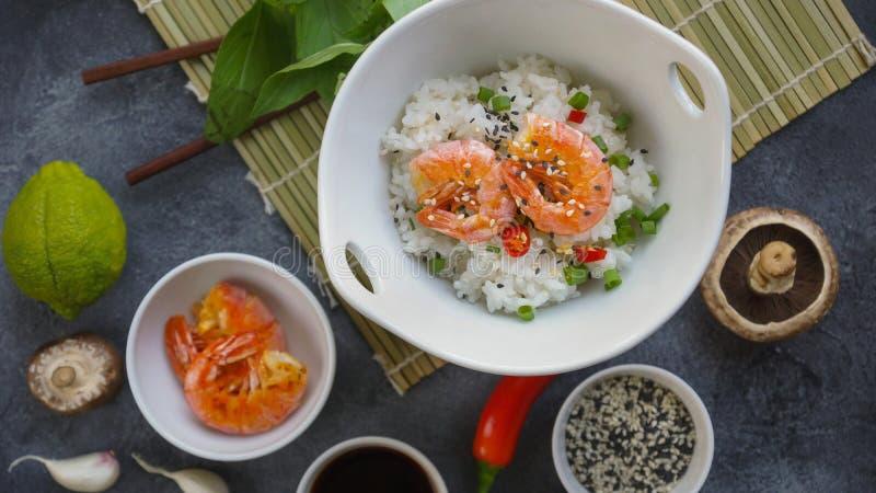Alimento asiático em um fundo escuro, no arroz do frigideira chinesa com camarões e nos cogumelos, durante a preparação imagens de stock