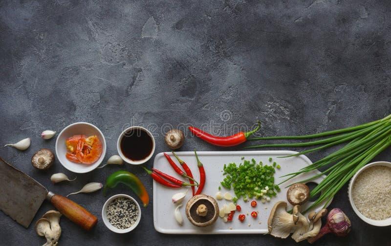 Alimento asiático em um fundo escuro, no arroz do frigideira chinesa com camarões e nos cogumelos, durante a preparação fotografia de stock royalty free