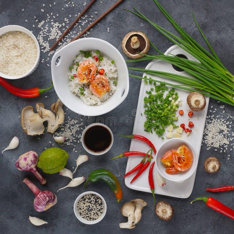 Alimento asiático em um fundo escuro, no arroz do frigideira chinesa com camarões e nos cogumelos, durante a preparação fotos de stock