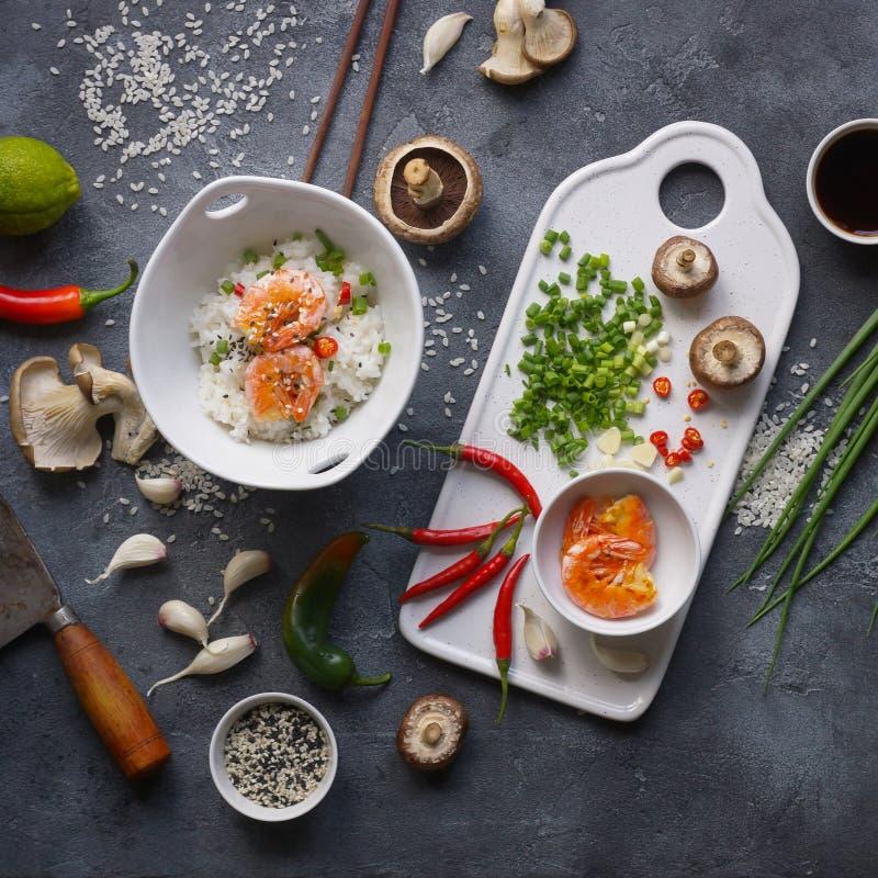 Alimento asiático em um fundo escuro, no arroz do frigideira chinesa com camarões e nos cogumelos, durante a preparação fotos de stock royalty free