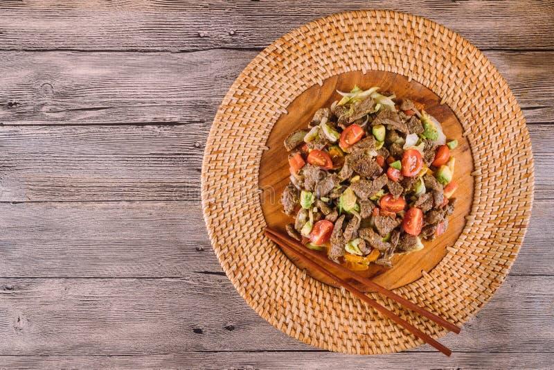 Alimento asi?tico Carne fritada com vegetais em uma placa de madeira fotografia de stock