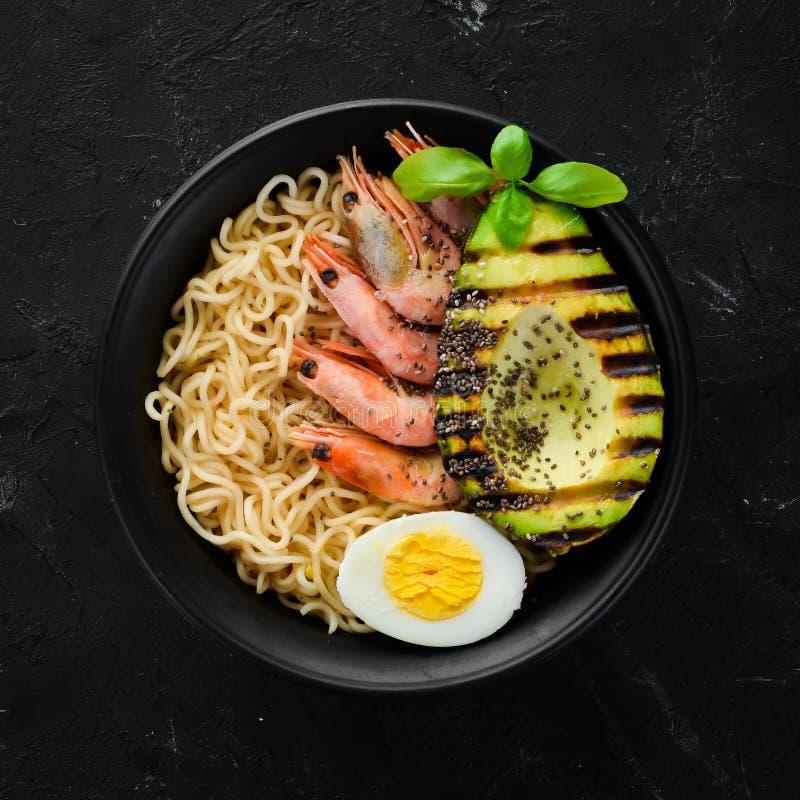 Alimento asi?tico Macarronetes com camarões, abacates, ovos e sementes do chia Em um fundo de pedra preto fotos de stock