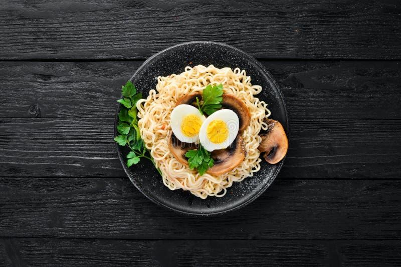 Alimento asi?tico Macarronetes com cogumelos, ovos e sementes do chia Em um fundo de madeira imagem de stock