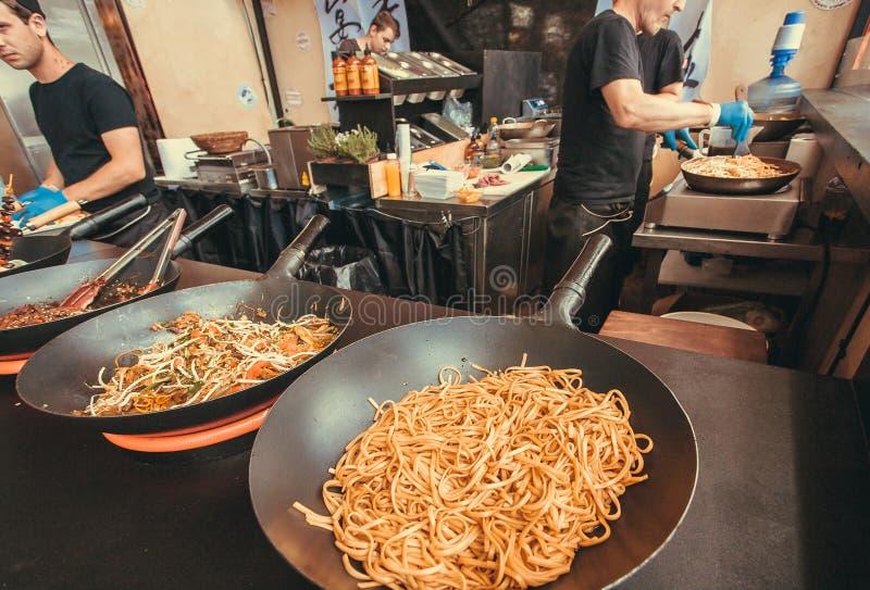 Alimento asiatico con le padelle piene di vermicelli in un caffè durante il festival all'aperto popolare dell'alimento della via fotografie stock libere da diritti