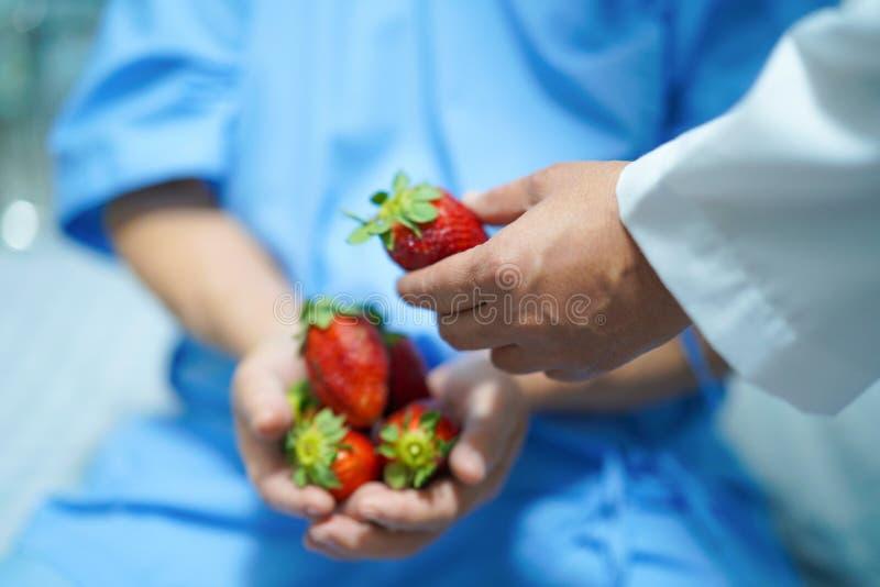 Alimento asiatico della signora anziana della donna del paziente della tenuta della frutta senior o anziana della fragola con spe immagine stock libera da diritti