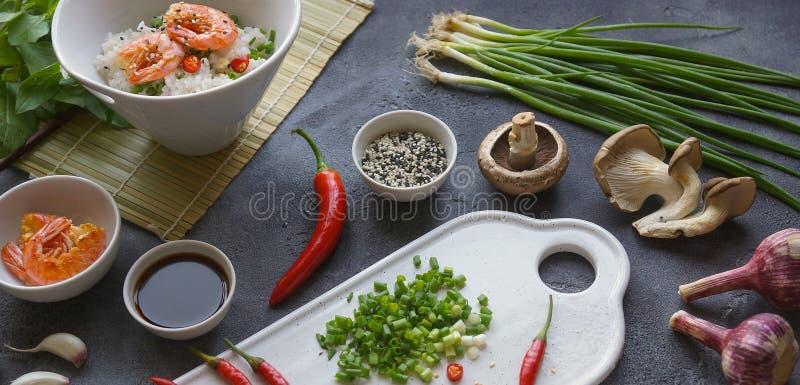 Alimento asiatico su un fondo scuro, sul riso del wok con i gamberetti e sui funghi, durante la preparazione, orizzontalmente, in fotografia stock
