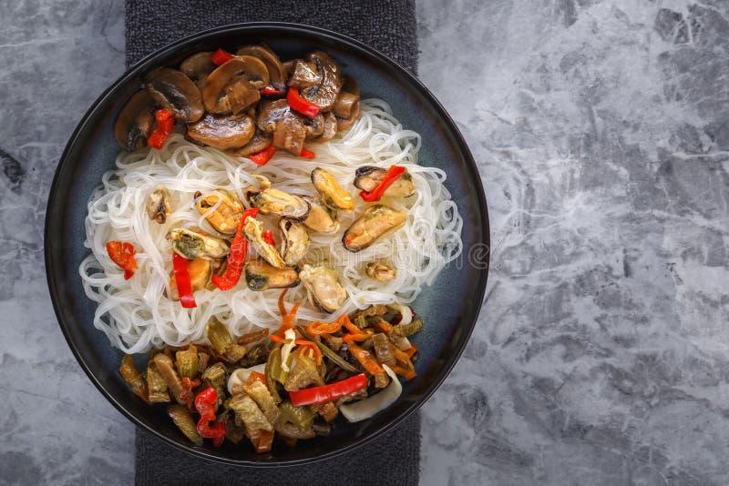 Alimento asiatico tradizionale - le tagliatelle di riso con frutti di mare, insalata, peperone ed i funghi fritti sono sulla tavo fotografie stock
