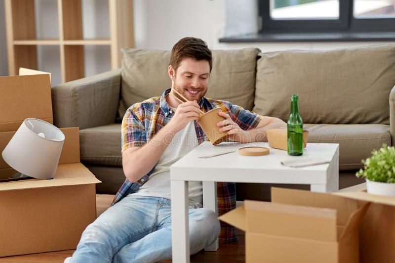 Alimento asportabile mangiatore di uomini sorridente a nuova casa fotografia stock