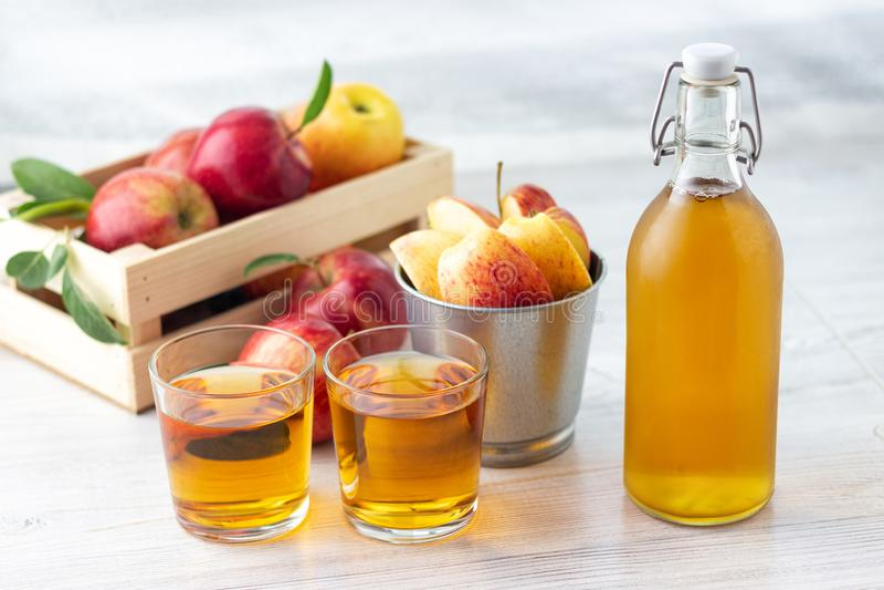 Alimento biol?gico sano Vinagre o jugo de sidra de Apple en la botella de cristal y manzanas rojas frescas fotografía de archivo libre de regalías