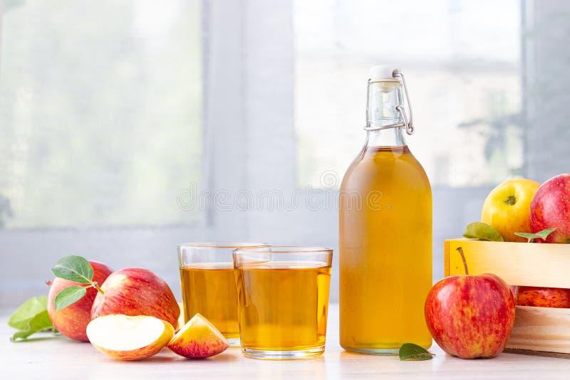Alimento biol?gico saud?vel Vinagre ou suco de sidra de maçã na garrafa de vidro e em maçãs vermelhas frescas foto de stock royalty free