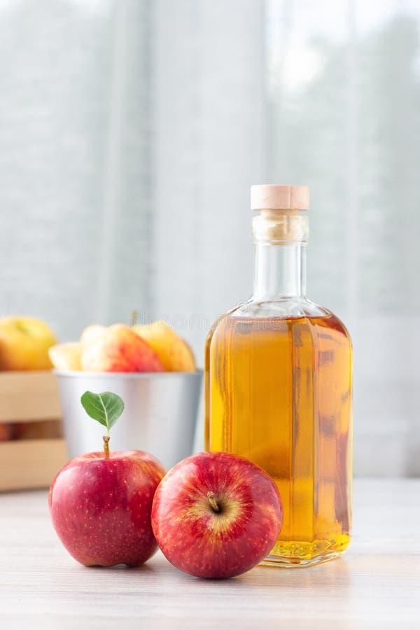 Alimento biologico sano Aceto o succo di sidro di Apple in bottiglia di vetro ed in mele rosse fresche fotografia stock
