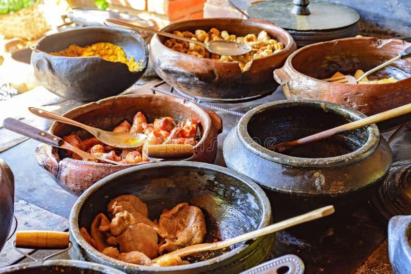 Alimento brasileiro tradicional que está sendo preparado em uns potenciômetros de argila imagens de stock royalty free