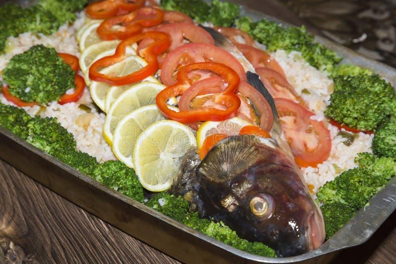 Alimento caseiro saboroso saudável Prato apetitoso da vitamina dos peixes com vegetais Carpa crua do rio enchida com arroz, tomat imagens de stock royalty free
