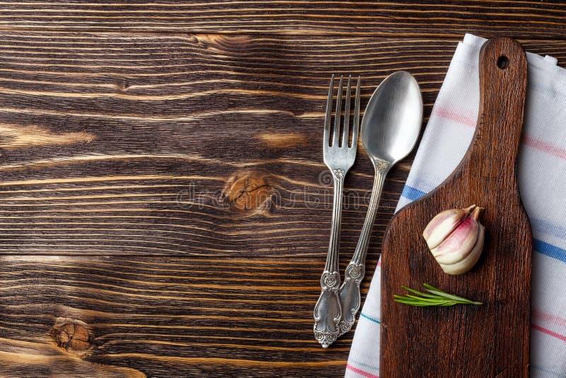 Alimento che cucina fondo con il tagliere, la coltelleria e le spezie di legno Vista superiore immagine stock libera da diritti