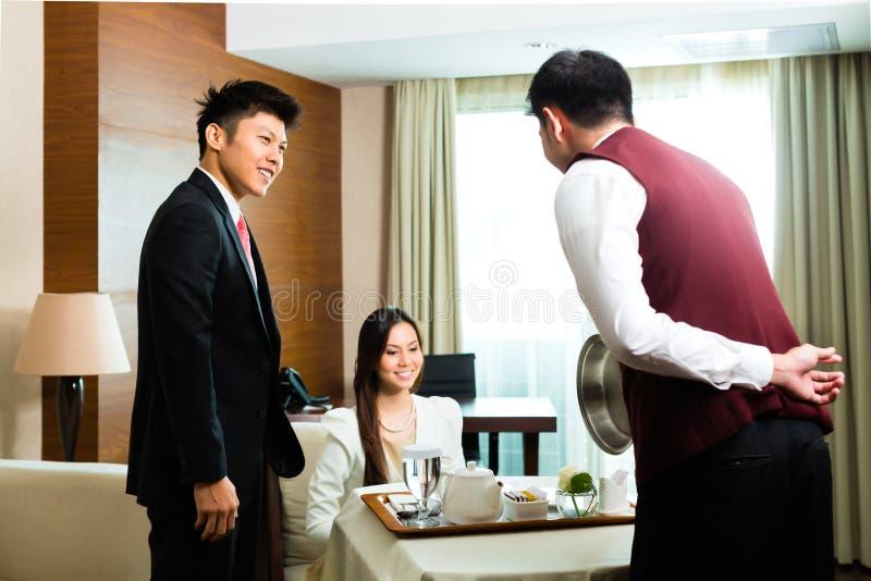 Alimento chinês asiático do serviço do garçom da sala na série de hotel imagens de stock royalty free