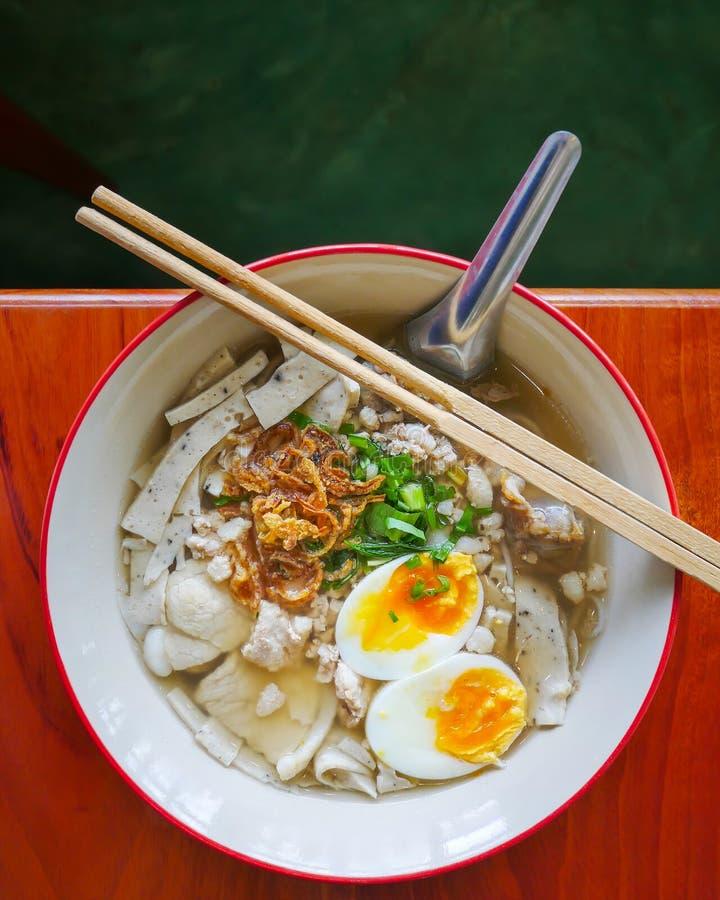 Alimento chinês tradicional em Tailândia pela vista superior, macarronete branco local na canja de galinha com cobertura do ovo c fotografia de stock