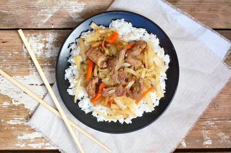 Alimento cinese con riso, la carota, il cavolo e la carne sulla banda nera su fondo di legno immagini stock libere da diritti