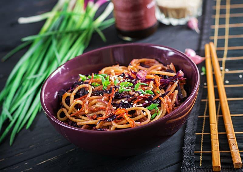 Alimento cinese Tagliatelle della frittura di scalpore del vegano con cavolo rosso e la carota immagine stock