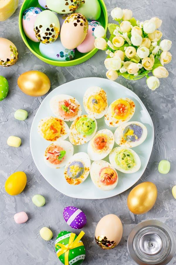Alimento colorido engraçado da Páscoa para crianças com as decorações na tabela Conceito do jantar da Páscoa imagens de stock
