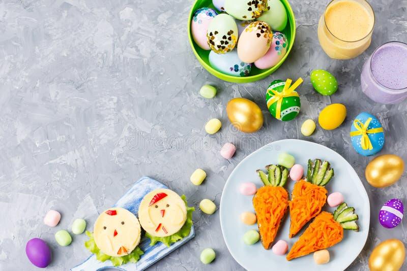 Alimento colorido engraçado da Páscoa para crianças com as decorações na tabela Conceito do jantar da Páscoa imagem de stock royalty free