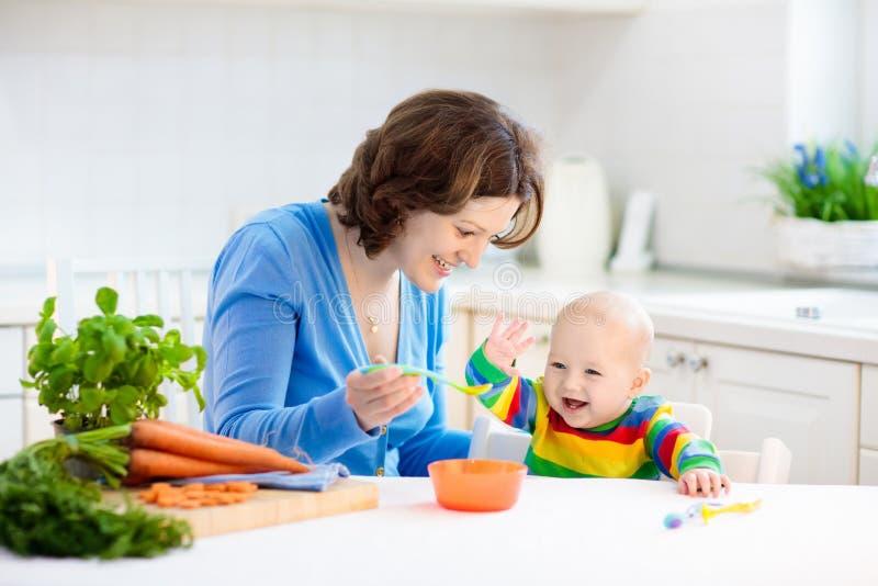 Alimento contínuo de alimentação do bebê da mãe primeiro foto de stock