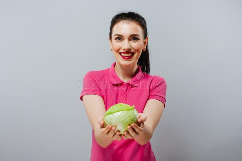 Alimento crudo, concetto della verdura Ritratto di bella ragazza sorridente in abbigliamento casuale che rimanda cavolo rosso in  fotografia stock libera da diritti