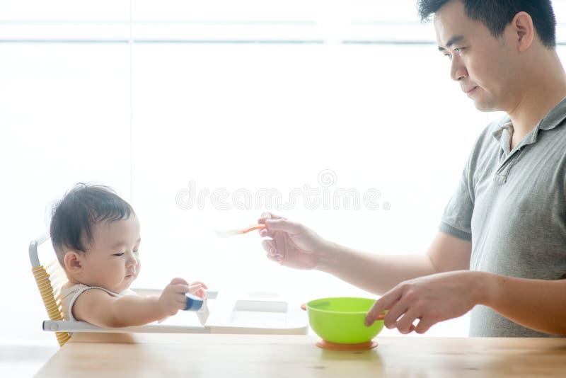 Alimento d'alimentazione del solido del bambino del padre fotografia stock libera da diritti
