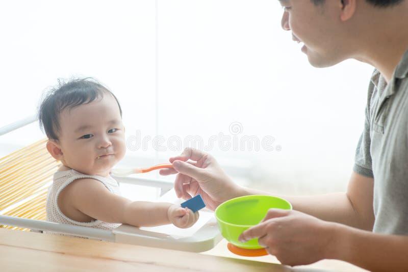 Alimento d'alimentazione del solido del bambino del padre fotografia stock