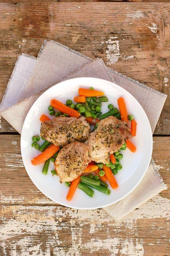 Alimento da faixa da carne de carne de porco com especiarias e as cenouras de bebê vegetais da mola, as ervilhas e os feijões ver fotografia de stock