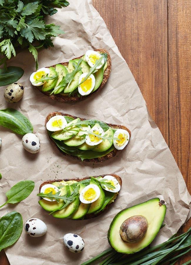 Alimento da mola Sanduíches com os ovos do abacate, dos espinafres, do guacamole e de codorniz no pergaminho Baixa dieta do hidra fotografia de stock