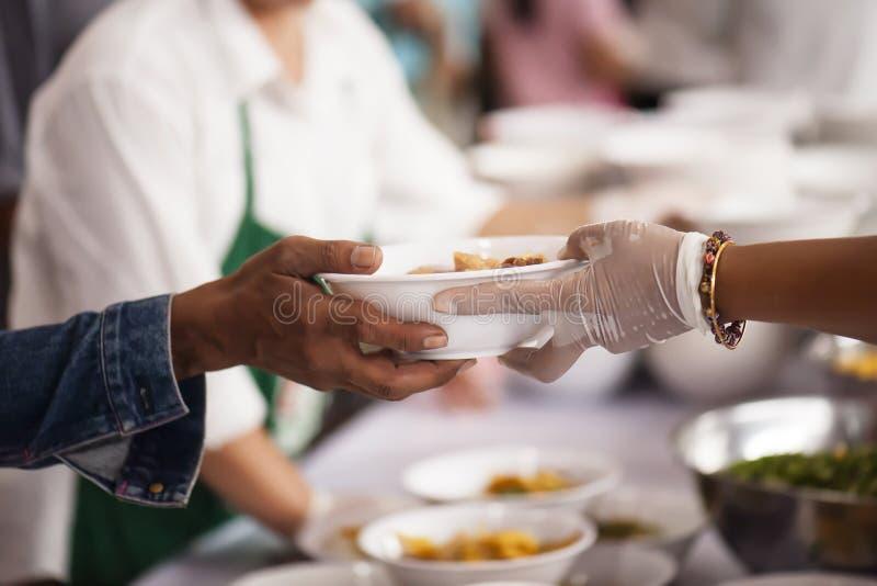 Alimento da parte dos voluntários aos pobres para aliviar a fome: Conceito da caridade imagens de stock royalty free