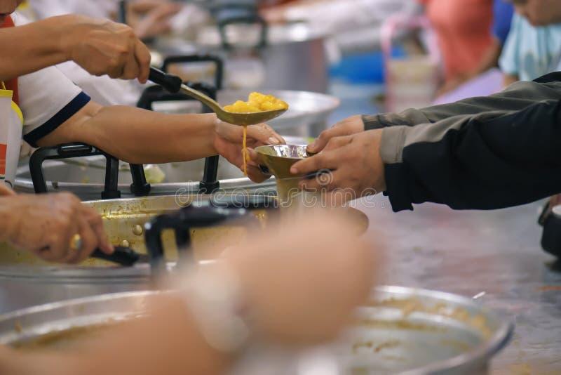Alimento da parte dos voluntários aos pobres para aliviar a fome: Conceito da caridade fotografia de stock royalty free