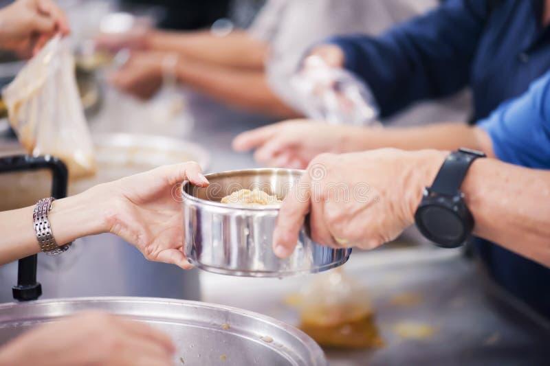 Alimento da parte dos voluntários aos pobres para aliviar a fome: Conceito da caridade imagens de stock