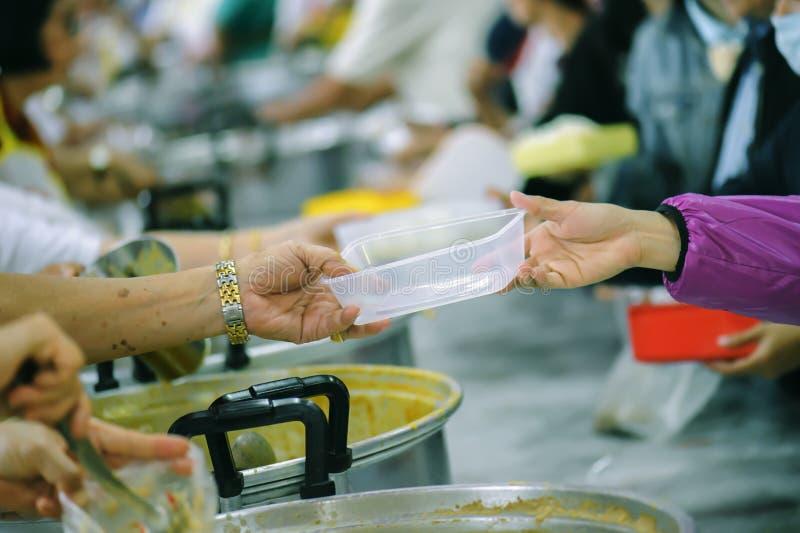 Alimento da parte dos voluntários aos pobres para aliviar a fome: Conceito da caridade imagem de stock royalty free